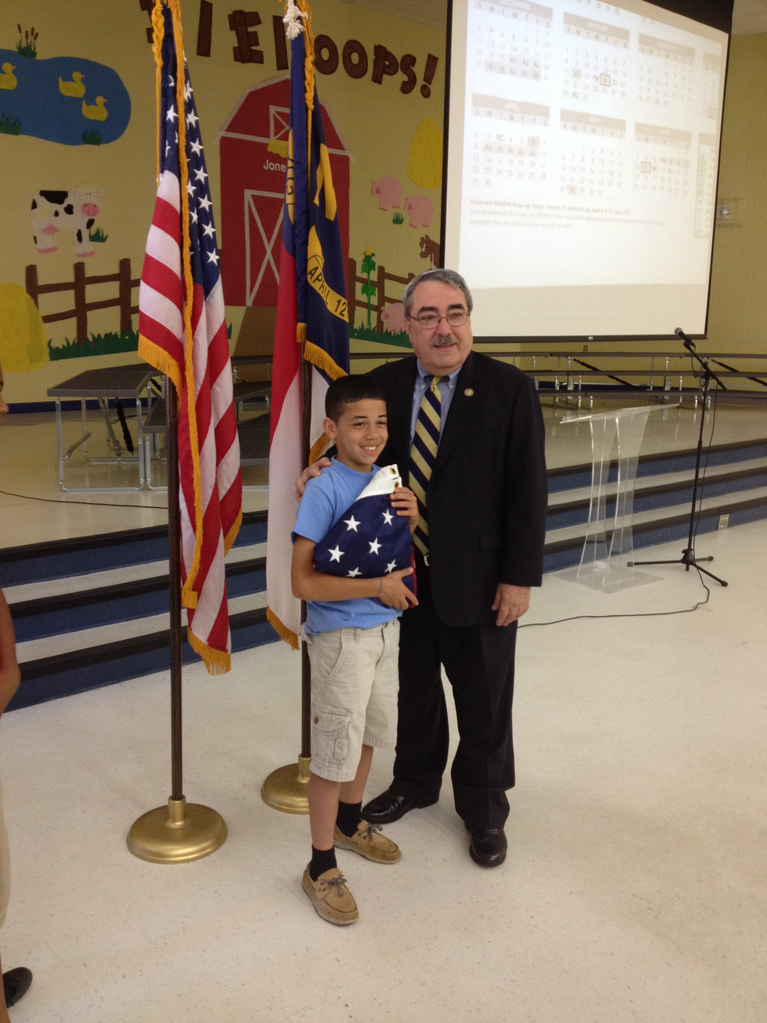 Congressman Butterfield presents a flag to a student at Jones Elementary in Wilson